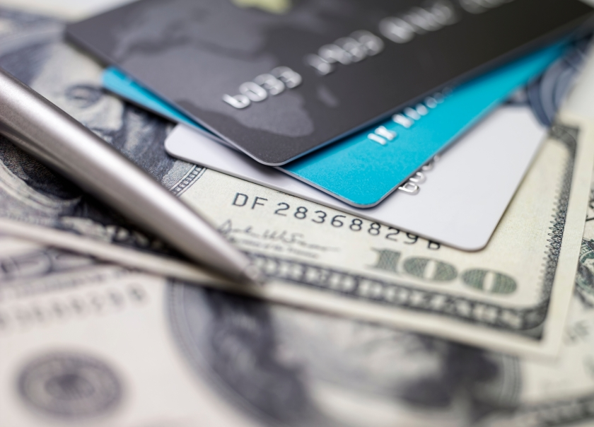 Three credit cards piled on top of dollar bills