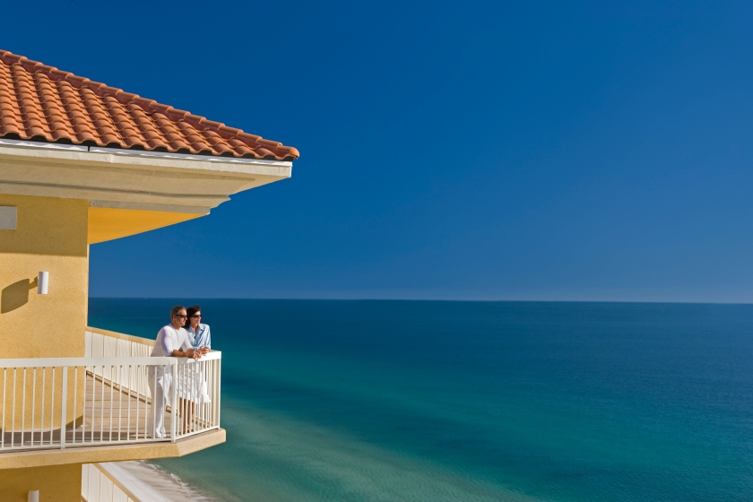 Couple Standing on Balcony Looking At The Ocean